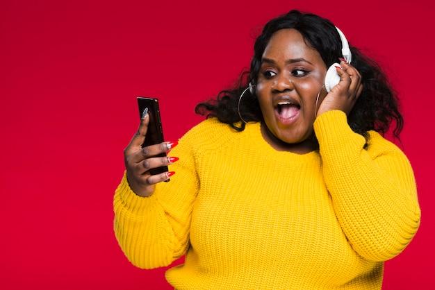 Высокий угол женщина прослушивания музыки на телефоне