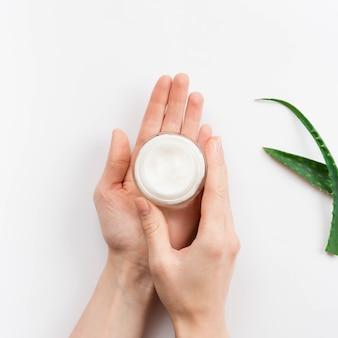 Руки держат крем для тела спа-концепцию