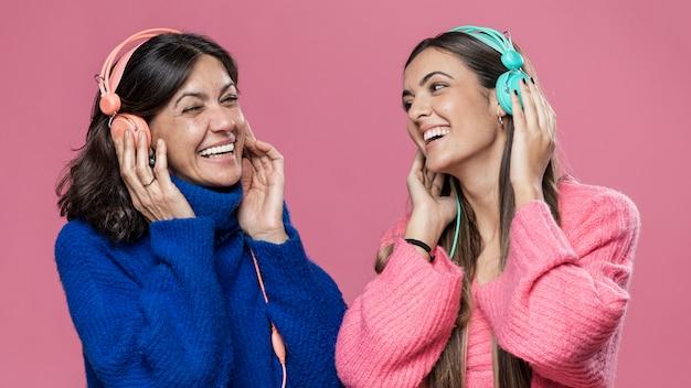 Низкий угол дочь и мать слушают музыку