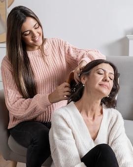 彼女のお母さんの髪を編む少女