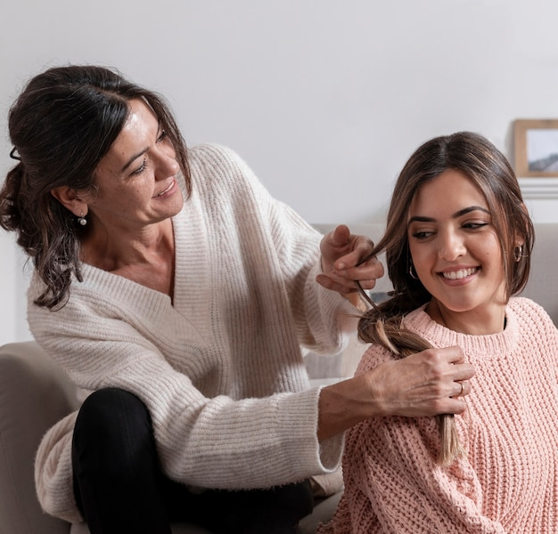 Улыбающаяся мама заплетает дочку в волосы
