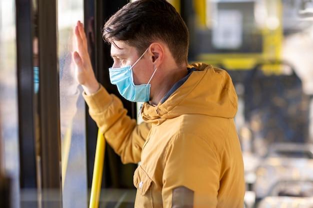 公共交通機関でサージカルマスクを持つ男