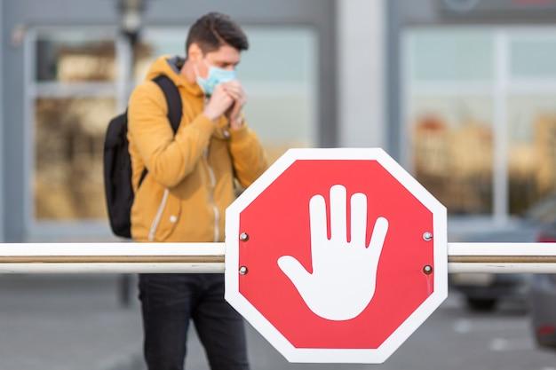 サージカルマスクと一時停止の標識を持つ男