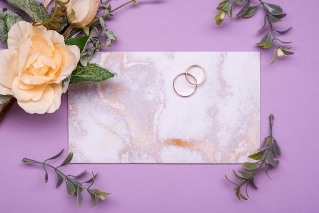Вид сверху элегантного свадебного приглашения в окружении цветов