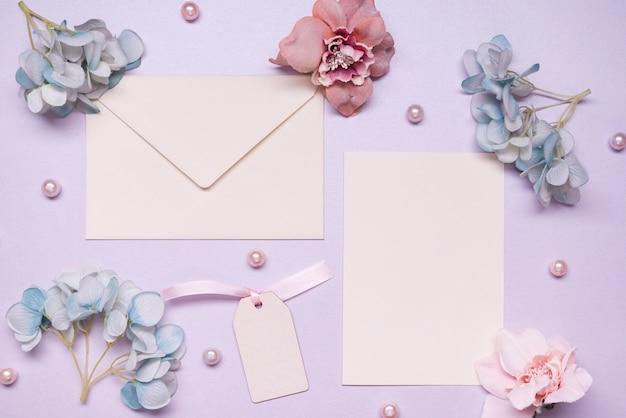 Вид сверху элегантный конверт с цветами на столе