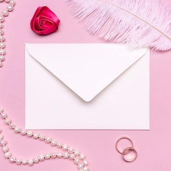 真珠と結婚指輪に囲まれたエレガントな封筒