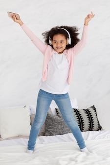 ベッドで音楽に合わせて踊る幸せな若い女の子の肖像画