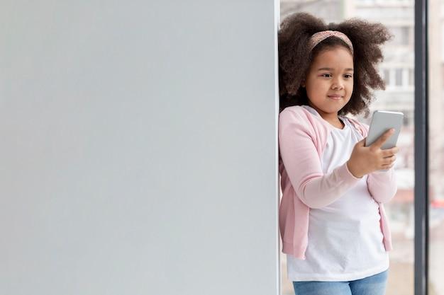 Портрет милая маленькая девочка держит мобильный телефон
