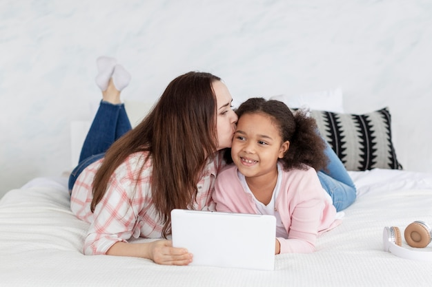 正面母親が娘と一緒に家で仕事をするのに満足