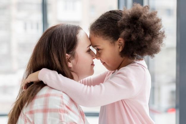Прелестная молодая девушка счастлива быть дома с матерью