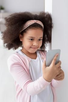携帯電話を保持しているかわいい若い女の子の肖像画