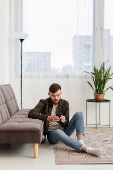 Молодой предприниматель просматривает мобильный телефон