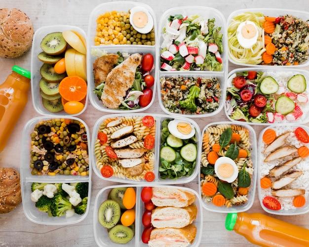 Плоско разложите вкусную еду в контейнерах