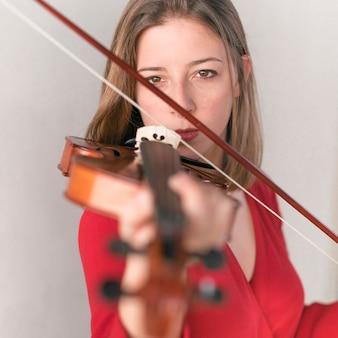 Расфокусированные скрипка играет женщина