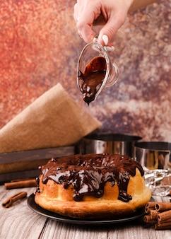Рука наливает шоколадный топинг на торт