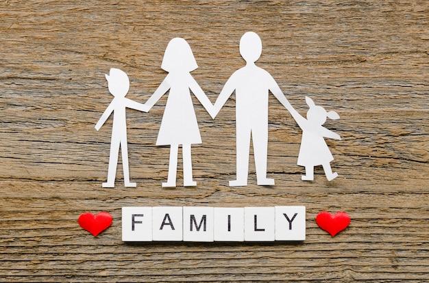 木製の背景の紙家族構成
