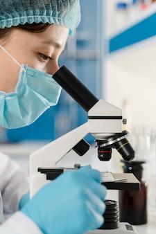 Молодая женщина химик, работающих с микроскопом