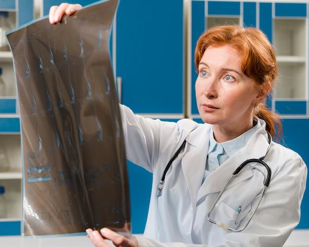 Средний снимок женщина-врач, глядя на рентген