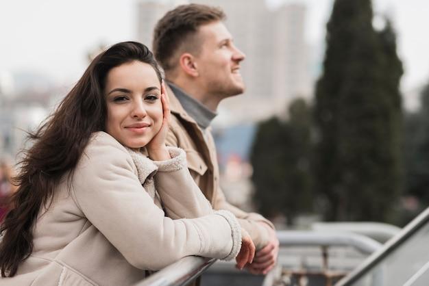 Женщина позирует с мужчиной на открытом воздухе