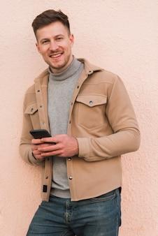 Красивый мужчина позирует, держа смартфон