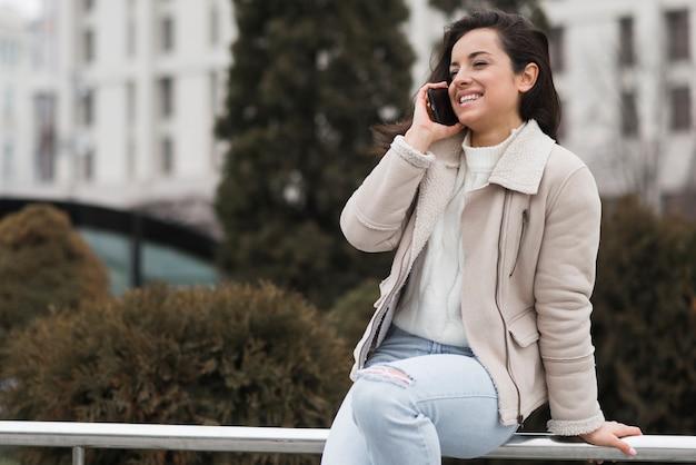 Женщина улыбается и разговаривает по телефону