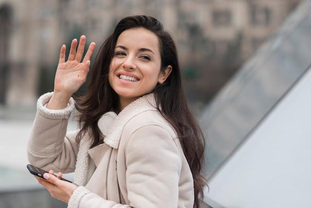 スマートフォンを押しながら手を振るスマイリー女性