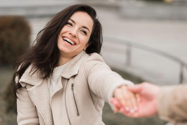屋外で男の手を保持している女性