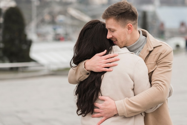 Мужчина обнимает женщину снаружи