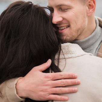 Улыбающийся мужчина обнимает женщину