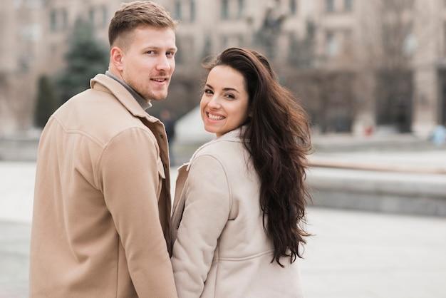 Улыбающаяся пара позирует на улице