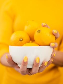 Женщина держит миску лимонов