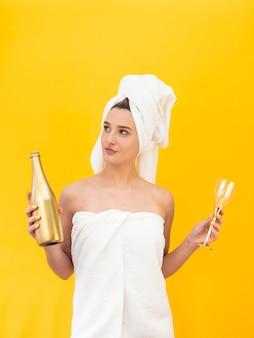 ボトルとガラスを保持している女性