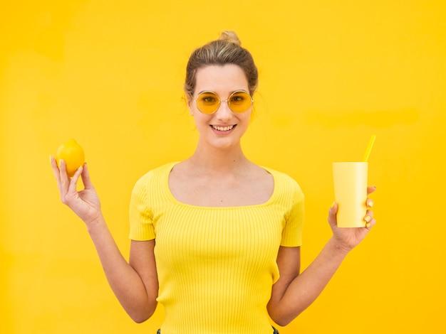 飲み物を保持しているミディアムショットの女性
