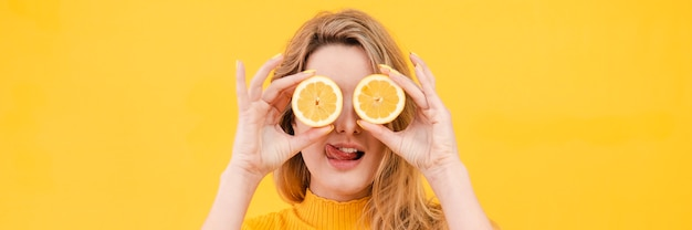 Молодая женщина, держащая апельсин