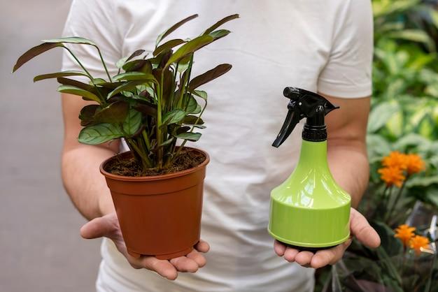 Мужчина держит комнатное растение и спрей бутылку