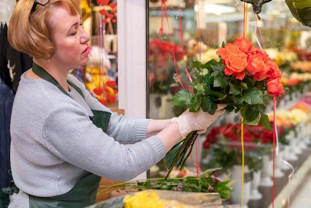 花束を保持している年配の女性