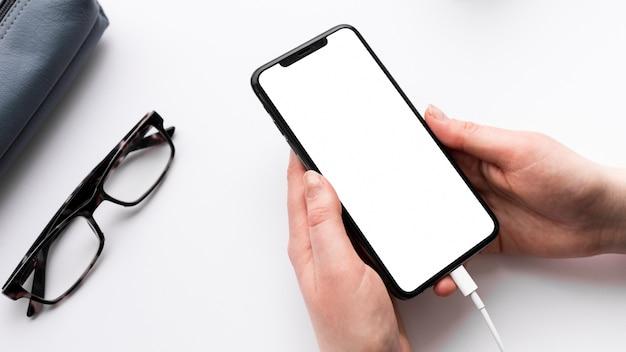 Человек высокого угла держа пустой дисплей телефона