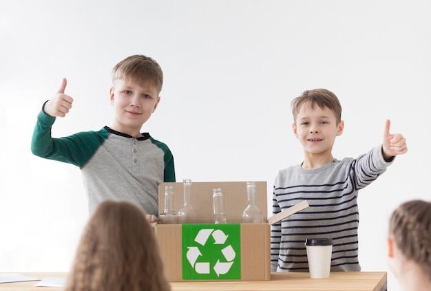 リサイクルして喜んでいる肯定的な若い男の子