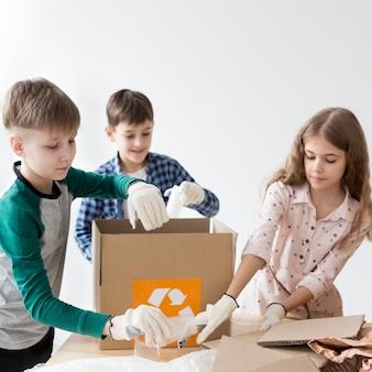 リサイクル方法を学ぶ幸せな子供たちのグループ