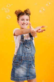 Улыбающаяся девушка играет с пузырьками