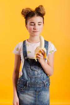 Молодая девушка ест банан