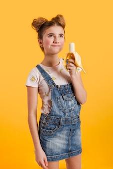 Вид сбоку девушка ест банан