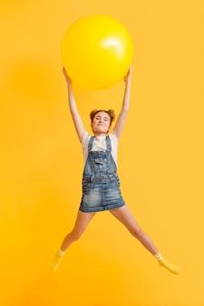 Маленькая девочка играет с мячом