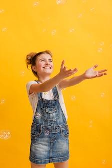 Девушка высокого угла милая играя с пузырями