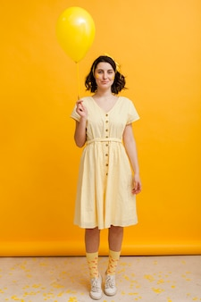 黄色のバルーンを保持しているハイアングルの女性