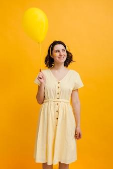 黄色のバルーンを保持しているスマイリー女性