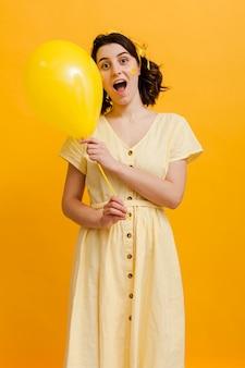 黄色の風船を保持している遊び心のある女性