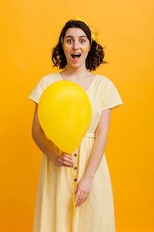 Молодая женщина держит желтый шар