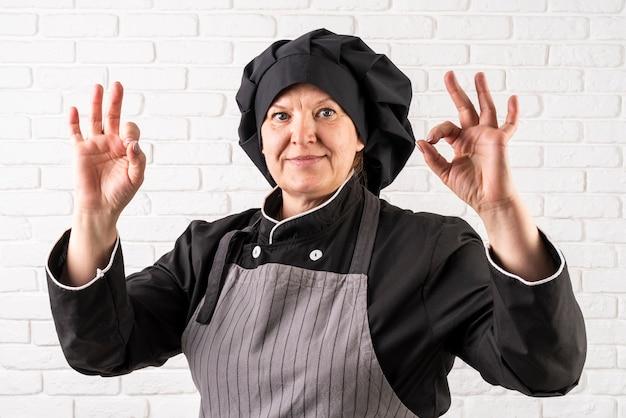Вид спереди женского шеф-повара, делая знак ок