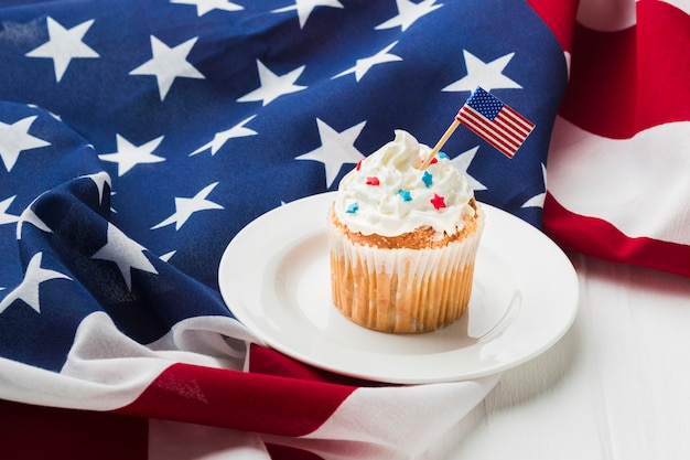 Высокий угол кекса на тарелку с американскими флагами